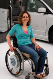 Woman in wheelchair posing in front of handicap accesible van